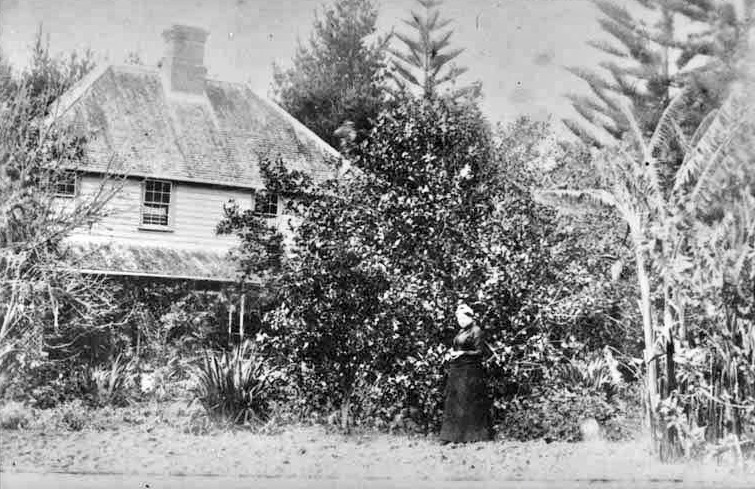 Showing William Innes Taylor's residence 'Glen Innes' which was built in 1849 in West Tamaki Road with Mrs Taylor in the garden on the western side of the homestead. Sir George Grey Special Collections, Auckland Libraries, 7-A1918